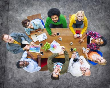Jahresrückblick von Die Bewerbungsschreiber: Team, das sich um einen Tisch herum bespricht, stellvertretend für das Team von Die Bewerbungsschreiber