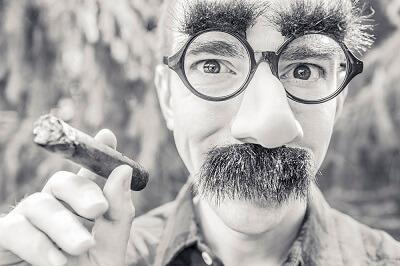 Schwarz-Weiß Bild Mann mit einer Brillen-Nase-Schnäuzer Maske und einer Zigarre in der Hand für Bewerber Typen Blender