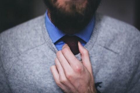 Close-up auf eine Hand, die eine Krawatte zurechtrückt: Zwischen zwei Jobangeboten wählen, mit allen Pro- und Kontra - Argumenten auf einen Blick