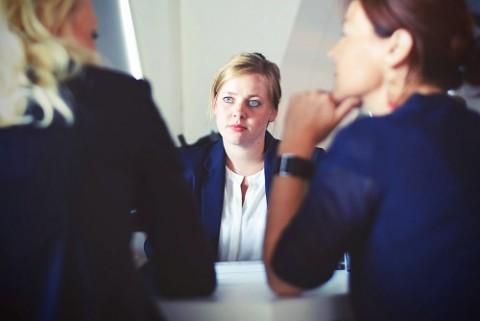 Drei Frauen in Anzug und Bluse befinden sich in einem Gespräch