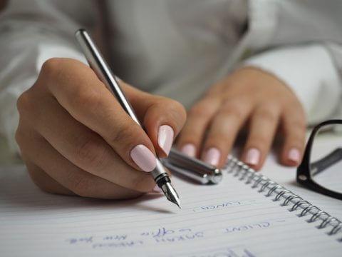 Zweifelhafte Bewerberauswahl - Grafologie - Frau schreibt einen Brief