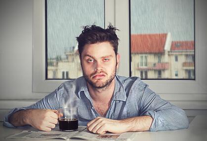Mürrischer Mensch mit Kaffeetasse