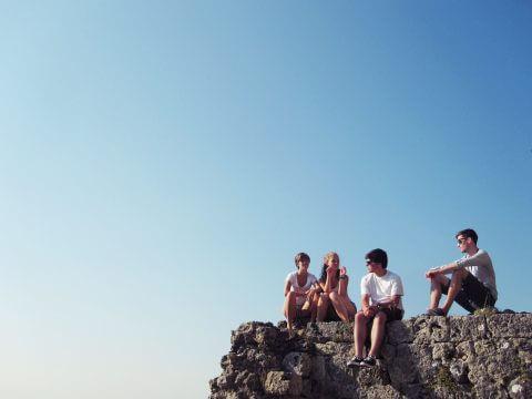Trainee-Einstieg - Absolventen sitzen ungewiss auf Felsen